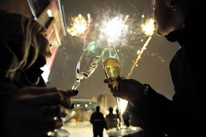 Two women toast as fireworks explode during an outside party in Berlin's Kreuzberg district to celebrate the New Year on January 1, 2010. AFP PHOTO DDP / TIMUR EMEK   GERMANY OUT (Photo credit should read TIMUR EMEK/AFP/Getty Images)