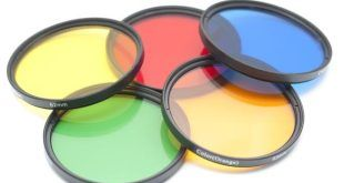 Close up on a set of five isolated color contrast photography lenses in yellow, red, blue, green and orange